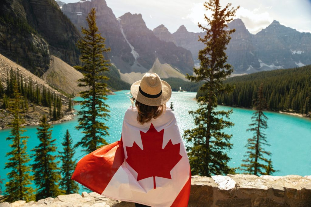Woman wearing a hat and Canada flag around shoulders in Banff