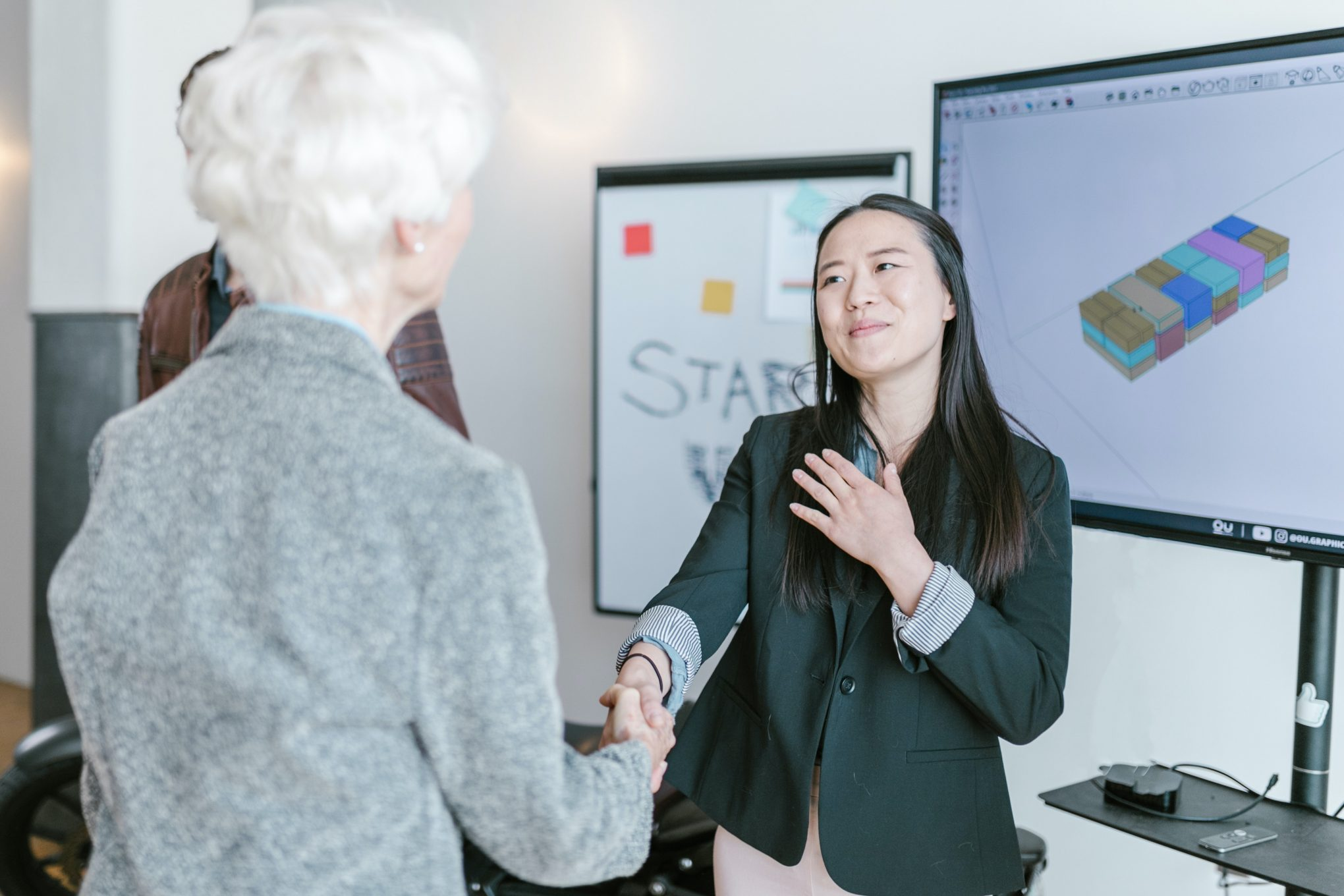 Asian woman shaking hands with elderly white woman